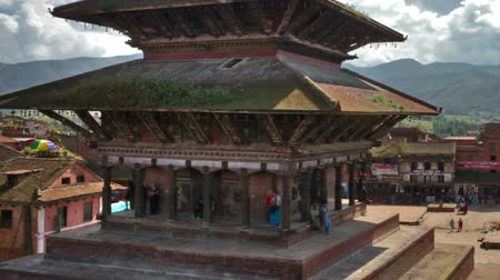 Time-lapse of Nyatapola temple in Bhaktapur, Nepal. The multi-storied pagoda and Taumadhi square are in the foreground with green hills in the background and white clouds in the blue sky. Panning shot.