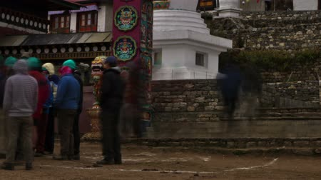 Time-lapse at the arched entrance to Tengboche Monastery in Nepal. People walk in and out of the gateway bordered by two lion statues. Cropped.