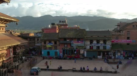 Time-lapse of dusk at Taumadhi square in Bhaktapur, Nepal. Bhairavnath temple is seen, as well as pedestrians walking through the plaza. Panning shot. Стоковые видеозаписи