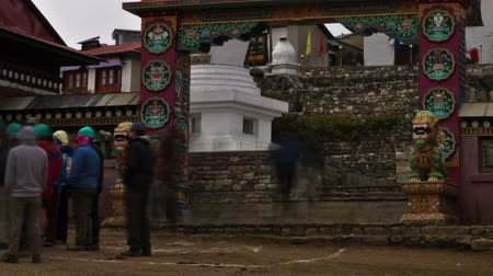Time-lapse at the arched entrance to Tengboche Monastery in Nepal. People walk in and out of the gateway bordered by two lion statues. Panning shot.