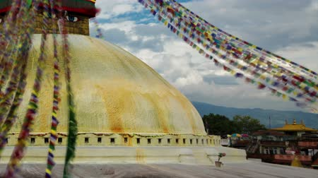 Time-lapse of Boudhanath Stupa in Boudha, Nepal. Colored prayer flags are streaming down from the point above the golden dome. Clouds are passing by in the blue sky overhead. Cropped. Стоковые видеозаписи