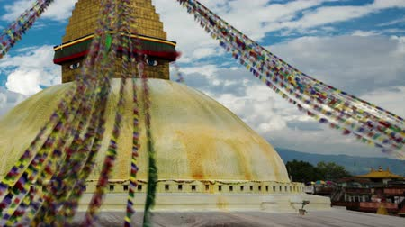 bodhnath : Time-lapse of Boudhanath Stupa in Boudha, Nepal. Colored prayer flags are streaming down from the point above the golden dome. Clouds are passing by in the blue sky overhead. Panning shot. Stock Footage