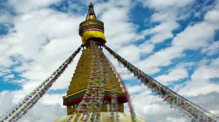 Time-lapse of Boudhanath Stupa in Boudha, Nepal. Colored prayer flags are streaming down from the point above the golden dome. People are walking around the base of the stupa. Clouds are passing by in the blue sky overhead. Cropped.