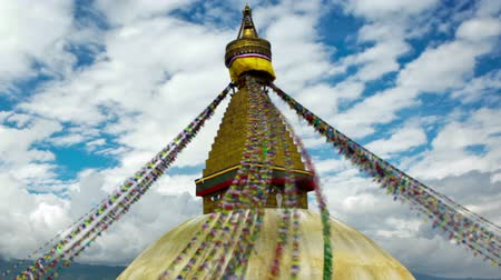 Time-lapse of Boudhanath Stupa in Boudha, Nepal. Colored prayer flags are streaming down from the point above the golden dome. People are walking around the base of the stupa. Clouds are passing by in the blue sky overhead. Panning shot.