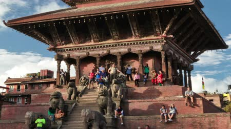Time-lapse of Nyatapola temple in Bhaktapur, Nepal. Statues line the stairs at the front of the multi-storied pagoda. White clouds pass by in the blue sky. Cropped.
