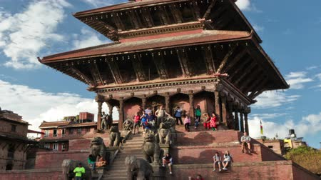 Time-lapse of Nyatapola temple in Bhaktapur, Nepal. Statues line the stairs at the front of the multi-storied pagoda. White clouds pass by in the blue sky. Panning shot. Стоковые видеозаписи
