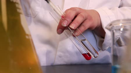 analisar : Closeup of a persons hands holding two test-tubes and transferring fluid from one to another