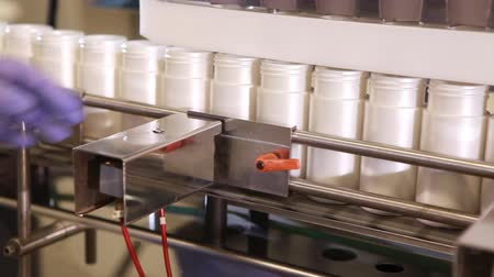 automatyka : Tracking shot of a a factory filling station with plastic bottles on a conveyor belt and a blue gloved hand moving them along. Wideo