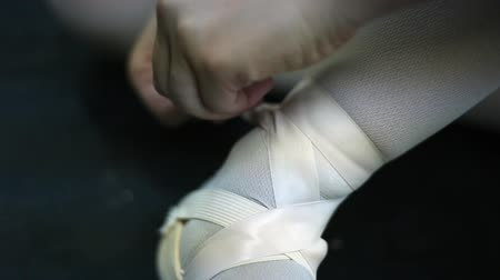 klapki : Closeup of a woman tightly fastening her ballet shoes with pink ribbons.