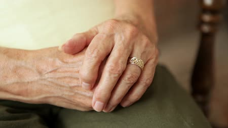 седые волосы : A close up shot of an elderly ladys clasped hands with her wedding ring in view. The wedding ring is a gold ban with an intricate design. Стоковые видеозаписи