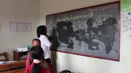 Мадагаскар : Mahajanga, Madagascar - CIRCA 2013 - Teacher erasing chalkboard with math equations written on it in classroom.