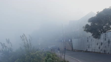 Мадагаскар : Mahajanga, Madagascar - CIRCA 2013 - Static shot of street as people are walking and fog blows through.