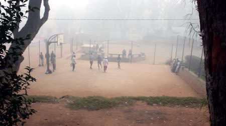 Мадагаскар : Mahajanga, Madagascar - CIRCA 2013 - Foggy view of young men playing basketball on a dirt court.