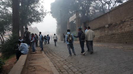 aboriginal : Mahajanga, Madagascar - CIRCA 2013 - Foggy view of teenage kids hanging out on the street as they are going to schoool. Stock Footage