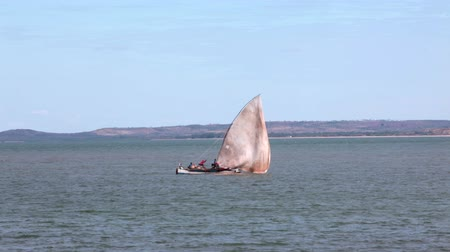 Мадагаскар : Mahajanga, Madagascar - CIRCA 2013 - Static shot of sailboat floating by as the wind blows its sail.