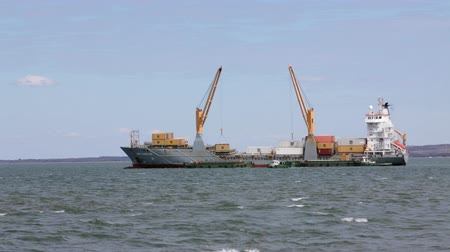Мадагаскар : Mahajanga, Madagascar - CIRCA 2013 - Static shot of freightliner ship loading smaller ships out in the ocean. Стоковые видеозаписи