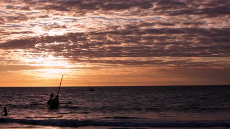 Мадагаскар : Mahajanga, Madagascar - CIRCA 2013 - Colorful sunset overlooking the ocean as sail boats are floating in the water.