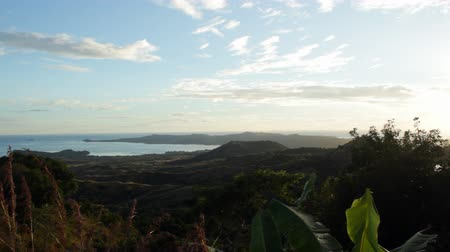 Мадагаскар : Mahajanga, Madagascar - CIRCA 2013 - View from the top of a hill overlooking the landscape toward the ocean as a slight breeze blows the leaves on trees. Стоковые видеозаписи