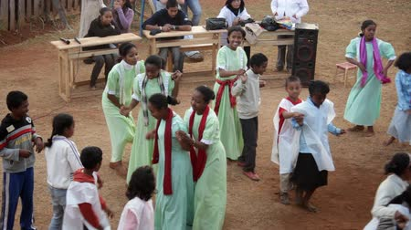 Мадагаскар : Mahajanga, Madagascar - CIRCA 2013 - Static view of young kids performing for others and dancing.