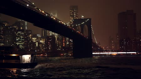 centrum : Shot at night overlooking the East River and the Brooklyn Bridge as a boat crusies by.