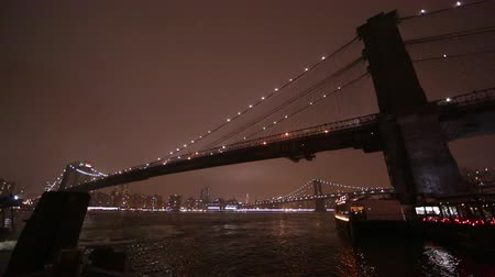 pomost : Shot at night overlooking the East River and the Brooklyn Bridge as a boat crusies by.