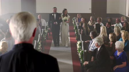 esküvő : Father escorting his daughter a bride down the aisle of a church at her wedding ceremony. He kisses her on the cheek and sits on a pew. The bride smiling steps up to the foreground preacher. A man on the front row makes a comment to his wife. The groom is