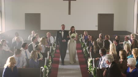 clergy : Father escorting his daughter a bride down the aisle of a church at her wedding ceremony. He kisses her on the cheek and sits on a pew. Despite the missing groom the bride smiles and steps up to the foreground preacher. A man on the front row makes a comm Stock Footage