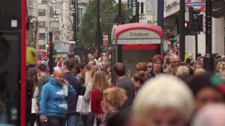 parecer : Stationary shot of busy Oxford Street full of people walking and cars and buses passing. A red phone booth also in the scene. The shot has been slightly slowed down so people and vehicles seem to move in slow motion. Filmed on October 8 2011.