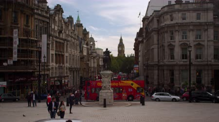 králové : A stationary shot of street traffic close to Trafalgar Square. There are people, double-decker buses, taxis, and cars. Big Ben clock tower can be seen in the distance among with other buildings on either side of the street. Filmed on October 9, 2011. Dostupné videozáznamy