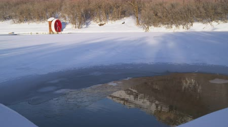 distante : Distant footage of a red water wheel on the edge of snow-covered frozen lake. A brown hill runs down to the edge of the pool and reflects in an unfozen patch of water. Stock Footage