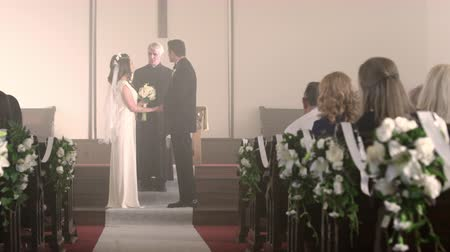 padre : Dolly shot moving from behind a pew to show a bride and groom walking down the aisle of a chapel towards a preacher.