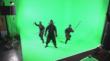 lutador : Static shot of three people dressed as ninjas posing in front of the camera Stock Footage