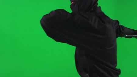 lutador : Slow motion green screen shot of a black ninja brandishing a katana