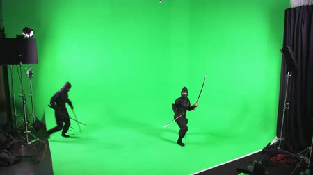 samuraj : Static shot of two people dressed as ninjas posing in front of the camera