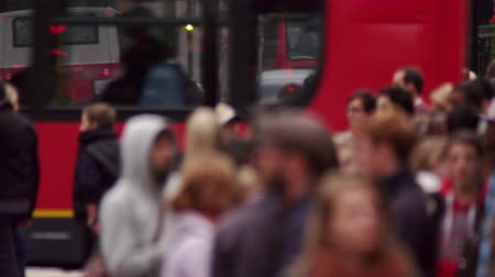 dvojitý : Stationary shot of crowded Oxford Street in North Soho London. People standing in the foreground are blurred the focus being on the traffic of cars and red buses in the background. The video is slightly slowed down. Filmed during daytime on October 8 2011