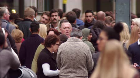 скрестив : A stationary slightly slowed shot of Oxford Street during rush hour. Some people stand and chat, others walk by. People closest to the camera are blurred. Filmed on October 8, 2011.