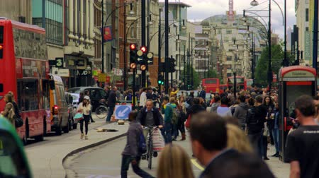 pěšina : A stationary shot of bustling Oxford Street in North Soho, London. People, buildings, traffic lights, lamp posts and traffic, mostly red double-decker buses, can be seen. Filmed during daytime on October 8, 2011.