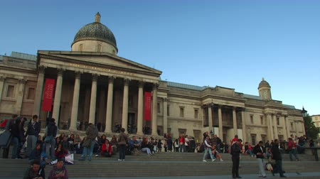 sütun : View of the people on the steps in front of the National Gallery art museum in London England at Trafalgar Square. Some people are taking pictures. There is a bright blue sky above. Shot on October 7 2011. Stok Video