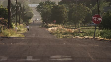 ciclismo : Static shot of dirt road. People are running and one is riding a bike. Car is visible driving towards camera. Stop sign and powerlines are also visible. FIlmed during the day.
