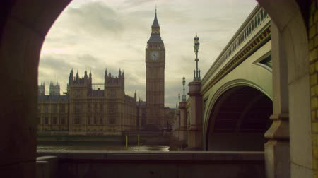 парламент : A stationary time-lapse shot of river Thames Westminster Palace and Big Ben clock tower in London. Captured from a tunnel next to Westminster Bridge. Some people pass the camera. Filmed on October 9 2011.