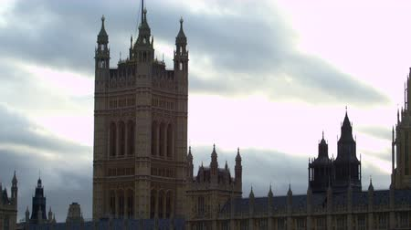 парламент : A panning view of the towers of Westminster Palace in London. The camera slides from left to right. Sky with some clouds constitutes the background. Filmed on October 9 2011.