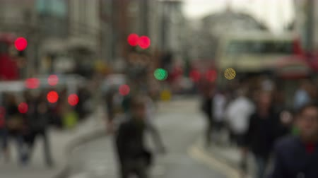 pěšina : A stationary shot of Oxford Street in North Soho, London. There are many people walking and some traffic. Traffic lights and double-deckers can be seen. The whole shot is blurred. Filmed on October 8, 2011. Dostupné videozáznamy