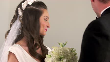 padre : Dolly shot moving around a bride and groom at the front of a chapel. They are facing each other as the preacher talks with them. They laugh. Rack focus from the preacher to the couple. Stock Footage