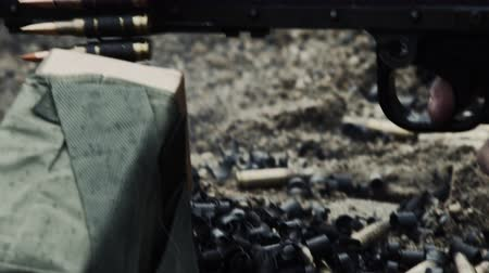 стрельба : Shot of a belt-fed machine gun as it is fired. Close-up on the chain of rounds moving to the pile of discarded casings and belt fragments. Smoke comes from the gun as it is shot. From a training for Green Beret United States Army Special Forces.