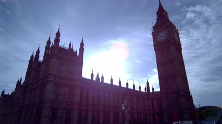 zajímavý : Stationary shot of Big Ben clock tower in London, filmed in the afternoon. The sunlight is dazzling and there are some clouds in the sky. In the corners of the scene, some interesting reflectins of surrounding people can be seen. Filmed on October 9, 2011 Dostupné videozáznamy