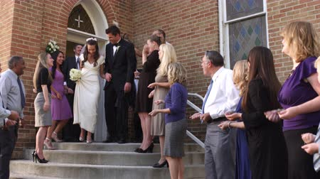 esküvő : Slow-motion shot of a bride and groom walking out of a church door and down steps as guests throw rice above them and applaud. Stock mozgókép