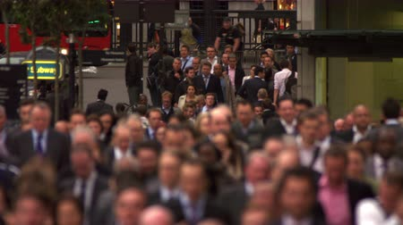 Businesspeople are commuting home after the end of their workday in London. They are walking down a crowded street. on the left some street traffic - cars taxis double-decker a group of cyclists - can be seen. People closer to the camera are blurred. Film Стоковые видеозаписи