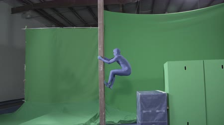 ginásio : Slow motion green screen shot of a man pretending to be a ninja climbing a pole
