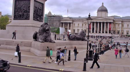 bronz : Slow motion stationary view of unidentified people near the Brass lion statues in Trafalgar Square, cars pass camera in foreground in London England. Filmed on October 11, 2011.
