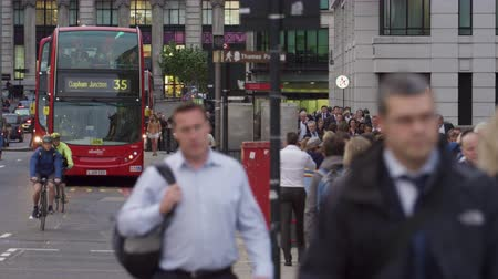 dvojitý : A stationary view of red double-decker buses departing from the bus stop on a busy street in London. People are walking on the sidewalk and cars and cyclists are passing by on the road. Filmed on an overcast day October 10 2011. Dostupné videozáznamy